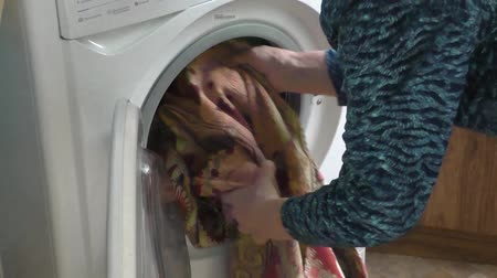 temperament : The elderly woman stacks dirty linen in the washing machine