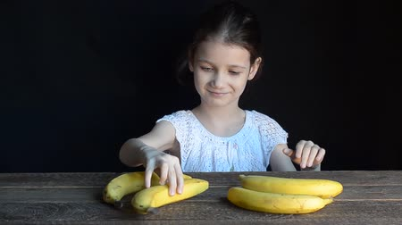 muz : Girl playing with bananas on the old wooden table. Black background