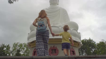 vacation : Happy tourists mother and her son in Long Son Pagoda. Travel to Asia concept. Traveling with a baby concept. Slow motion