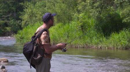 waders : Man fishing on a mountain river with a ultralight spinning using fishing wobblers