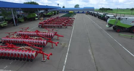 kombajn : low flying camera on trailers and ploughs to combine harvesters, located in the Parking lot for farm equipment