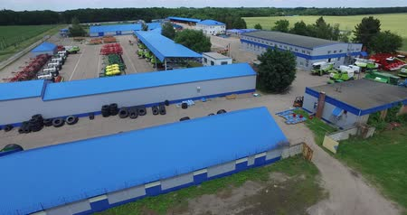 In the frame of the blue roofs of the technical facilities, combine harvesters, plows, tires for tractors Wideo