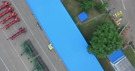 kombajn : panoramic camera movement from right to left diagonally on the blue roof of the warehouse and plows and trailers to the harvesters, standing on a concrete platform Wideo