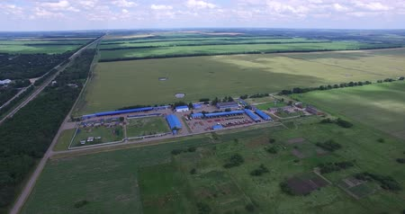 the territory of agro-industrial complex of technical buildings, fields planted with different crops, on the left frame and views of the road and a small settlement Dostupné videozáznamy