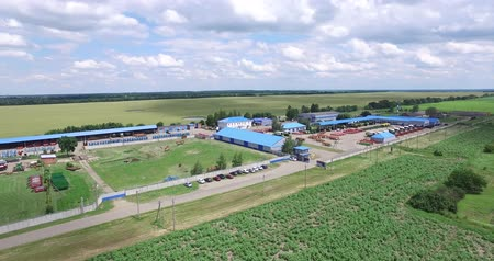 the camera moves over the fields, then approaching the technical buildings and the concrete pad on which the agricultural equipment Dostupné videozáznamy