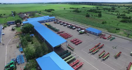 the territory of agro-industrial complex from a technical and administrative buildings, fields planted with different crops, hangars and sheds for combines and agricultural machinery Dostupné videozáznamy