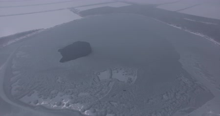 icy : A large lake in the fog, a camera flies over a frozen lake