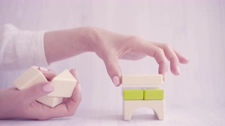 kurmak : Close up of woman hands establish or build a toy house with colorful wooden blocks. Strong family concept. Business growth, house loans or mortgage concept. Light background, soft focus, 4k UHD Stok Video