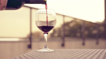 diner : Red wine poured into glass. Winery rooftop with small table and glass fence. Background in soft focus. 4k UHD
