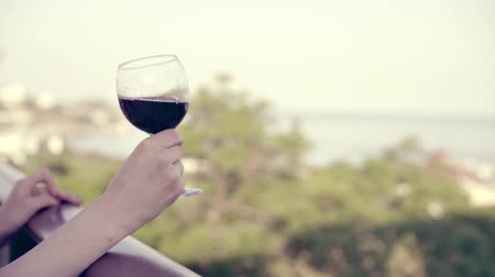 şarap kadehi : The woman hand hold a glass of red wine, on the winery terrace with a view to the sea. Girl slowly shake a glass with wine. Soft focus. 4k UHD