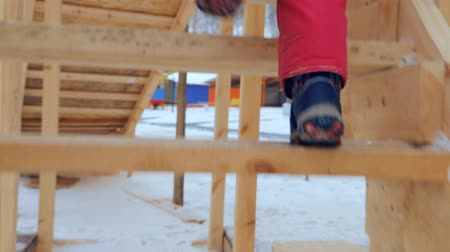склон : Child is climbing up slide stairs at playground