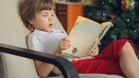 él : Small girl reading a book in front of Christmas tree