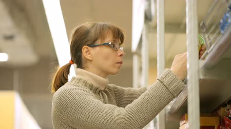 supermarket shelf : Woman choosing goods in supermarket