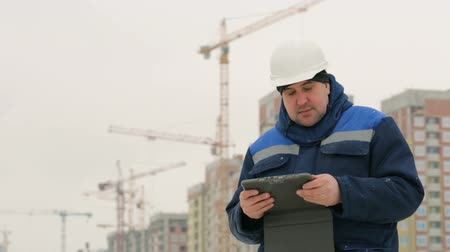 supervising : Foreman with pad at major construction project