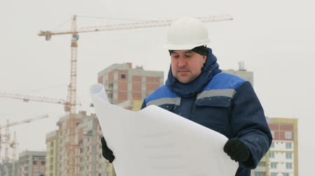 supervising : Foreman with paper drawing plan at construction project
