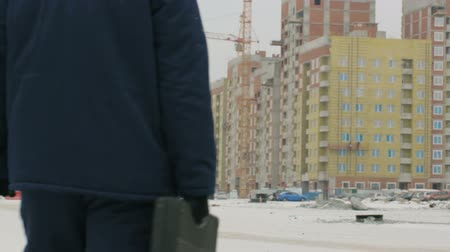 резидент : Foreman with brief case at major construction project
