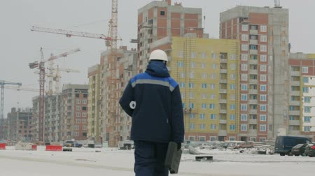 резидент : Foreman with brief case and drawings at construction project