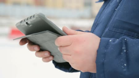 supervising : Electronic pad in male hands against building construction