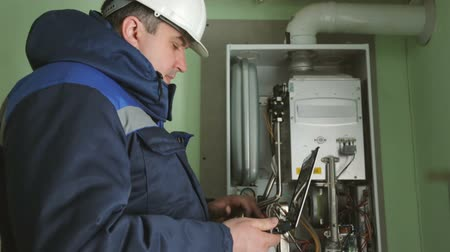 heating system : Worker checking gas-fire boiler