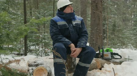 velo : Worker resting on log in winter forest