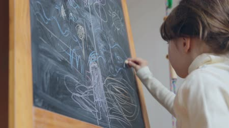 hand draws : Little girl drawing with chalk on board Stock Footage