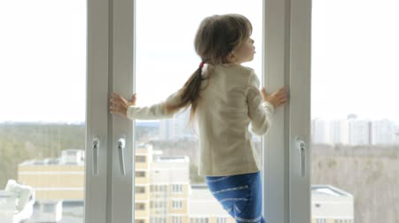 típico : Little girl on the windowsill