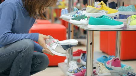 but : Woman choosing shoes at shoe store