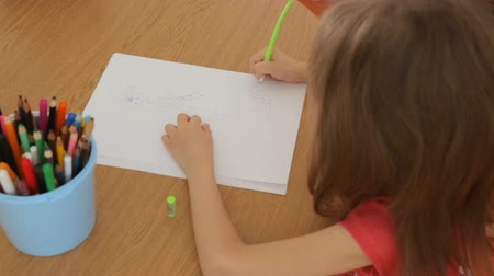 small pen : Little girl drawing pictures on paper