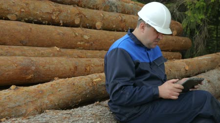 register : Worker with tablet PC sitting on pile of logs