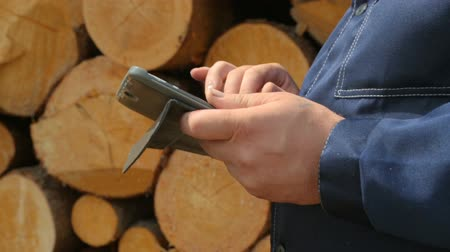 jegyzettömb : Worker with tablet PC against pile of logs Stock mozgókép