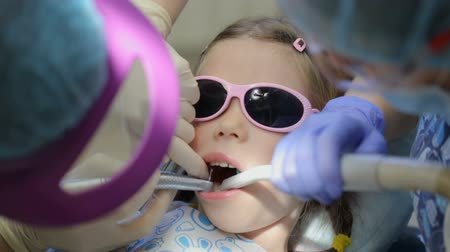 stomatological : Little girl in dentists chair having her tooth treated Stock Footage