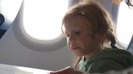 pigtail : Little girl with mother in the airplane Stock Footage