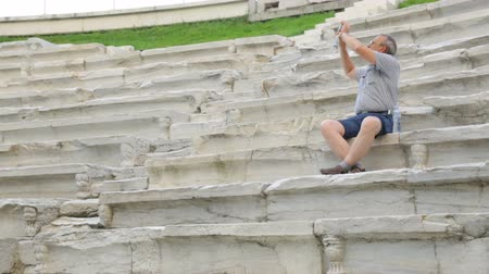 archeological : Male tourist filming in antique stadium