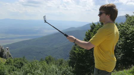 балканский : Young man making selfie on mountain