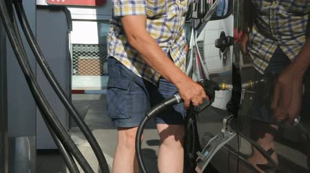 пистолеты : Driver refueling a car at a gas station
