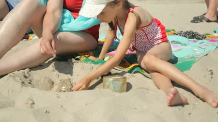 strandlaken : Woman and child playing with sand on beach