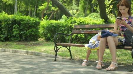 neglected : Woman with daughter in public park Stock Footage