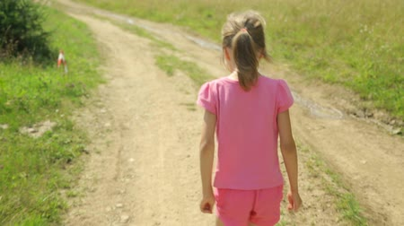 ahead : Little girl walking along a rural road