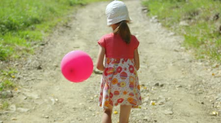 green grass : Little girl with pink balloon walking along a rural road