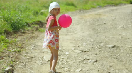 um : Little girl with pink balloon walking along a rural road