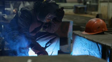 сварщик : Welder welding metalwork in a factory