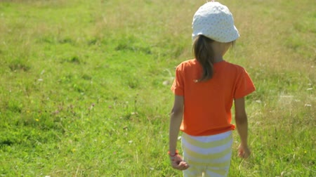 Little girl walking on a field Stock mozgókép
