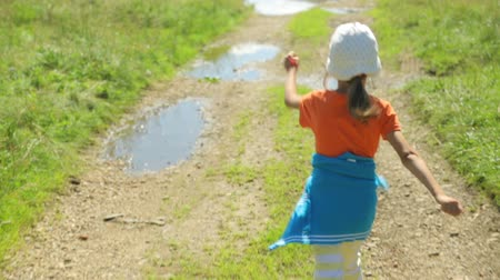 zöld fű : Little girl walking along a rural road
