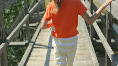 Little girl walking across an old bridge