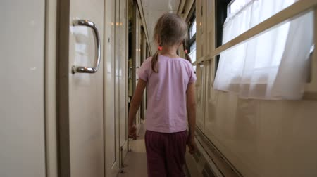 gangway : Little girl walking along an aisle in a train