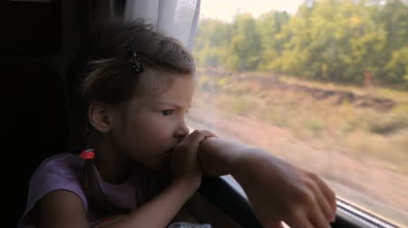 přihrádka : Little girl looking through the window in the train