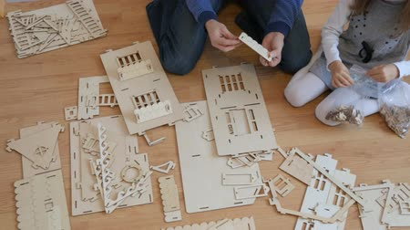 komplexní : Little girl with father building wooden toy house