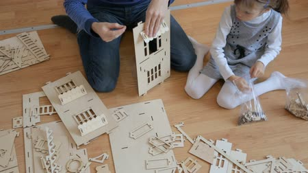 plywood : Little girl with father building wooden toy house