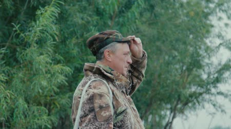 A close-up of a fisherman on the bank of a river taking off his headdress and staring into the distance against a green bush