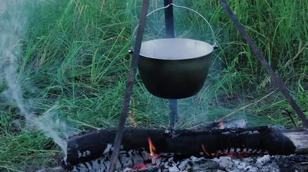 A close-up of a bowler hanging over a burning fire on a tripodCl Wideo